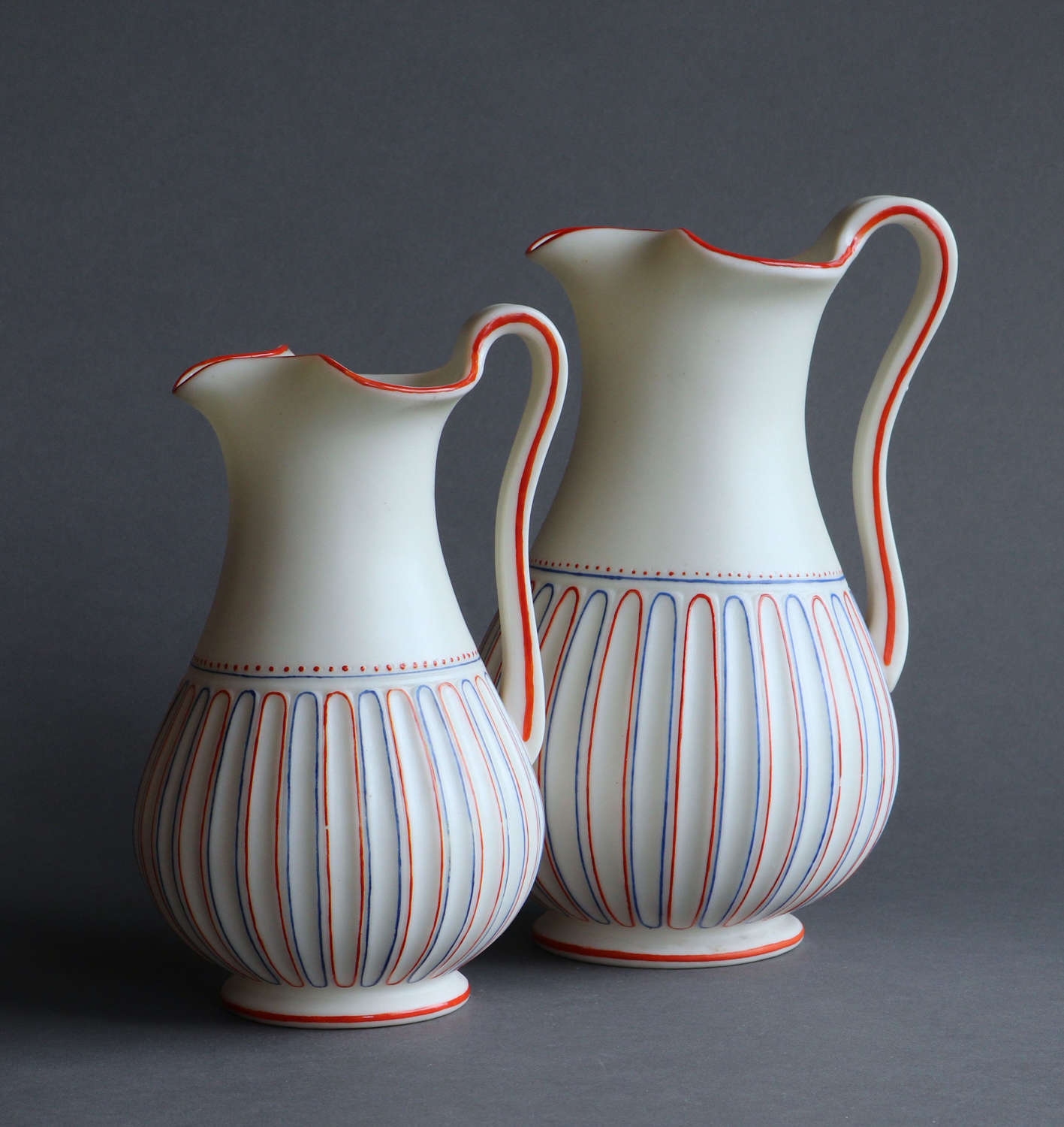 Two Worcester Parian decorated fluted lipped jugs